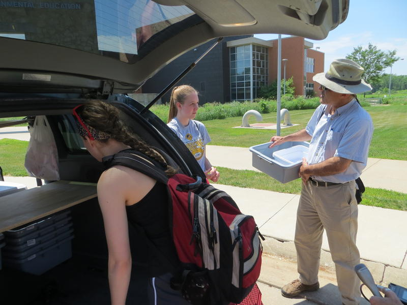UNI Professor Kamyar Enshayan helps the students prepare a minivan to transport vegetables to a mobile produce stand