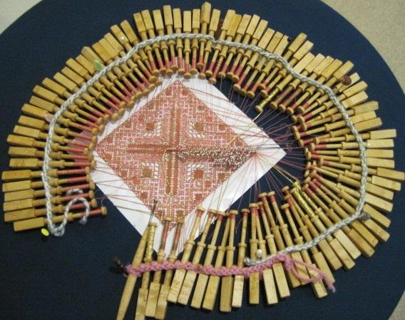a piece of bobbin lace being made