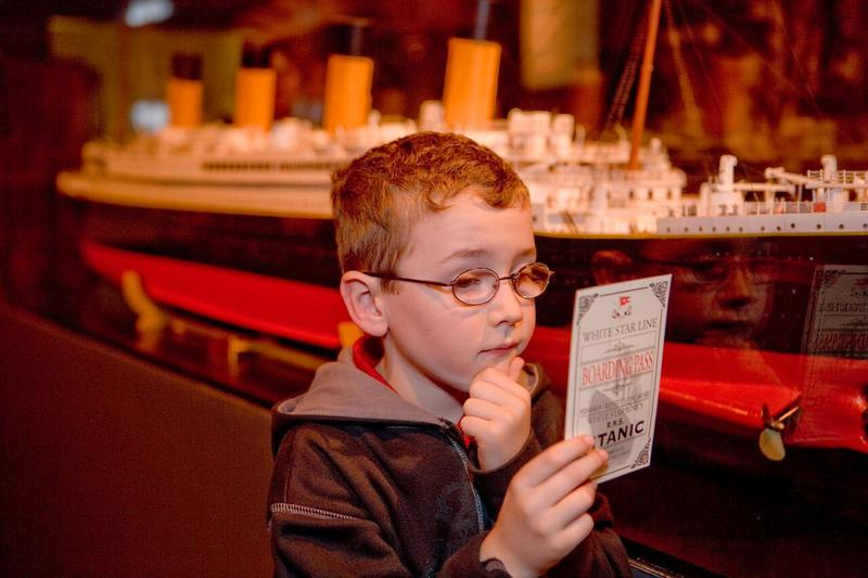 A boy reads the history of one of the passengers on board the Titanic, printed on a boarding pass.