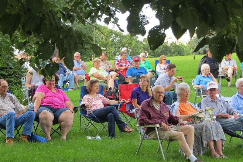 Fans settle in on the grassy hillside.