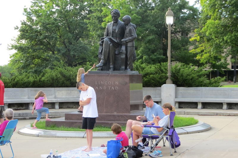 A family relaxes under the Lincoln monument.