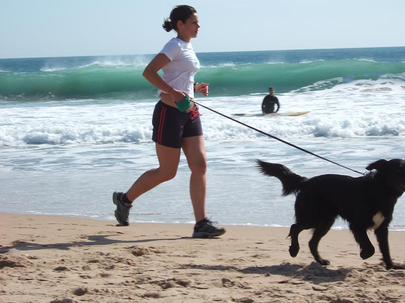 A woman and dog jog on the beach.