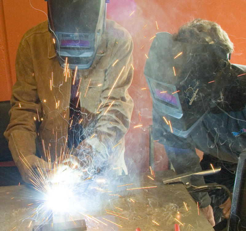 Students use a MIG welder on a steel part