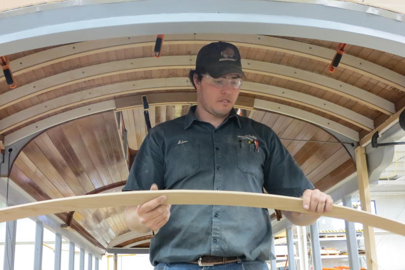 Woodworker installs new rafters in Taiwan car.