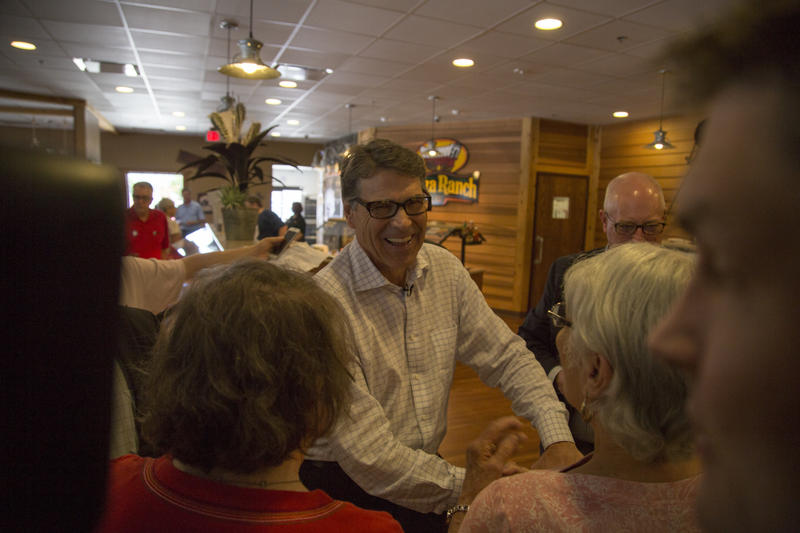 Former Texas Governor Rick Perry works a crowd at the Fort Dodge Pizza Ranch on July 17, 2015.