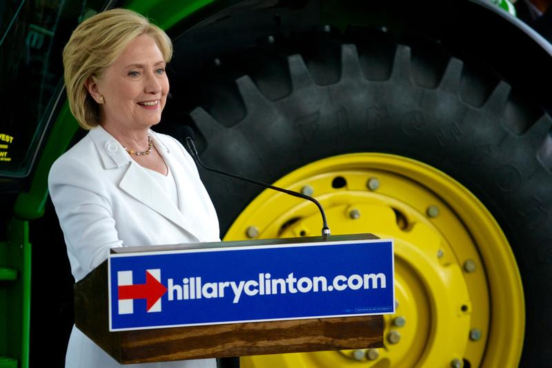 Hillary Clinton unveiling farm policy initiative with John Deere tractor as a backdrop at Des Moines Area Community College
