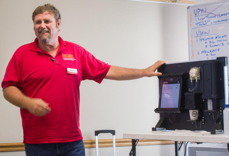 Carl Pederson, of Iowa State Extension, demonstrates a portable soil testing machine that can offer results of nitrogen content within minutes, right in a farmer's field.