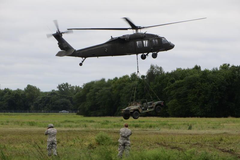 A Black Hawk lifts a Humvee during sling load training at Camp Dodge.