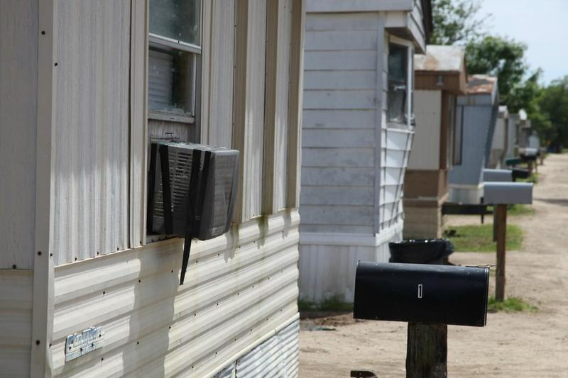 A dog rests in the shade at a trailer park that rents to farmworkers in Kennett, Mo.