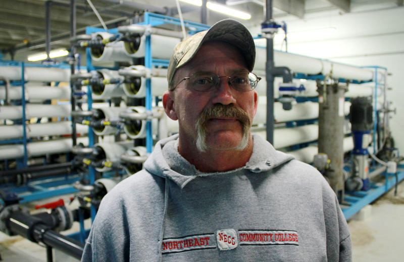 Creighton, Neb. water operator, Kevin Sonnichsen, stands before the $1.3 million reverse osmosis system that filters nitrates from the town's water.