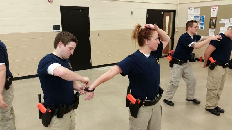 Iowa Law Enforcement Academy recruits practice handcuffing a suspect.
