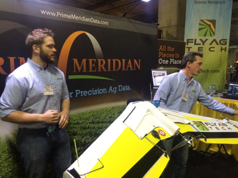 Casey Adams, left, and Scott Jackman, partners in Fly Ag Tech, show off their drone at the Western Farm Show in Kansas City.