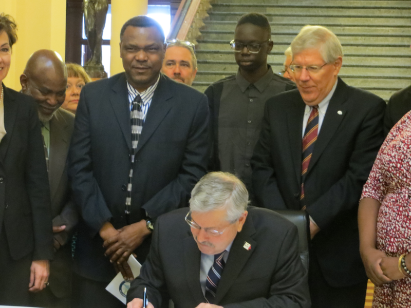 Governor Branstad signs legislation to keep juvenile court records confidential.   Branstad is accompanied by members of the NAACP