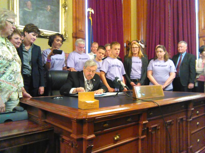"Gov. Terry Branstand signs SF 2218 into law, legalizing the administration of Naloxone by lay people. The bill's supports wear shirts that say, ""Got Naloxone?"""