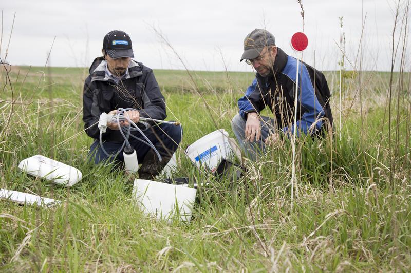 Iowa Soybean Association's Adam Kiel (left) collects  a water sample from landowner Lee Tesdell's bioreactor in Polk County