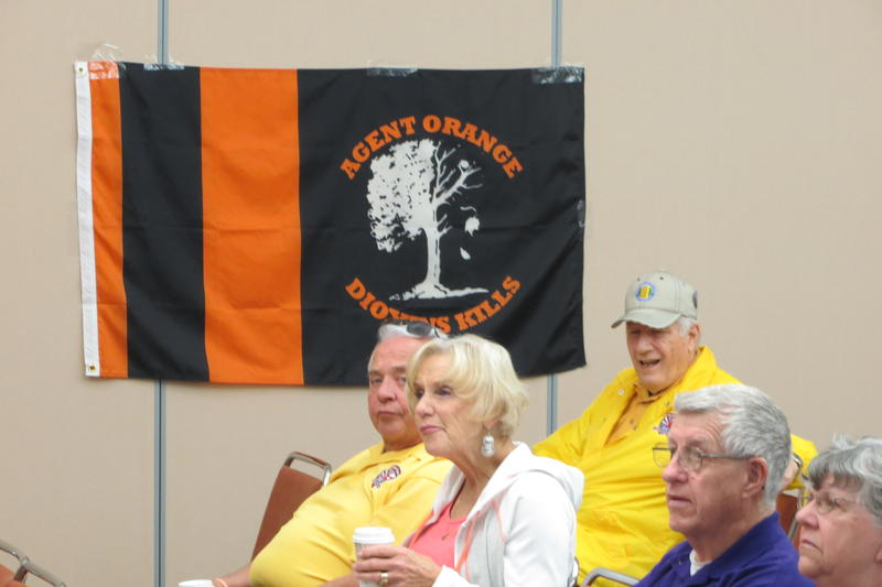 A banner symbolizes the Agent Orange issue, showing a tree half dead and half alive.