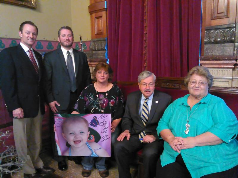 Jeri King holds a large photo of her late granddaughter, Kamryn Schlitter. Pictured left to right: State Rep. Ken Rizer (R-Cedar Rapids), Assistant Linn County Attorney Nick Maybanks, King, Gov. Terry Branstad, and King's sister Vickie Mayo.