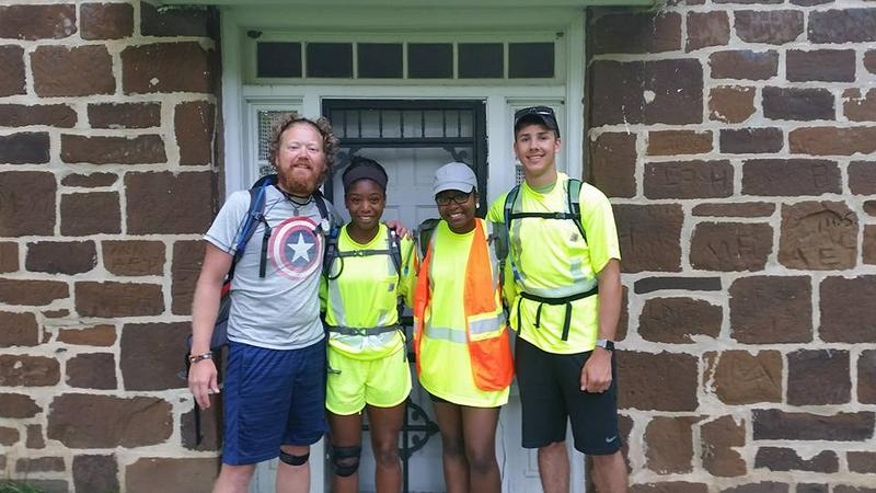 Barry Jurgensen poses for a picture along the route with three of his students who are making the walk with him