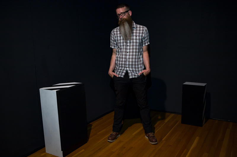 "In a dark room at the Des Moines Art Center, Alex Braidwood stands by one of six speakers generating sound for his audio art piece ""Listen Right Here: DSM."""