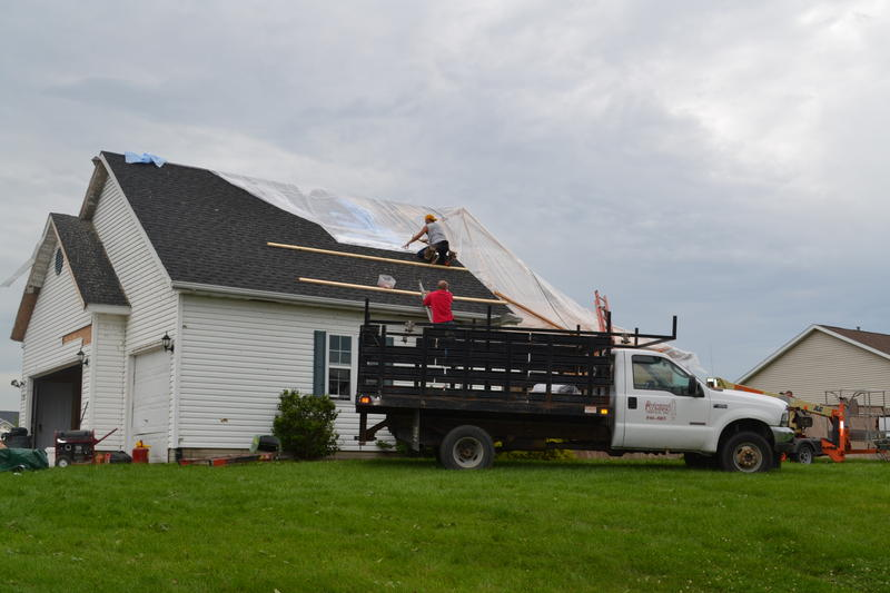 Crews cover storm damanged roofs of other Walford homes