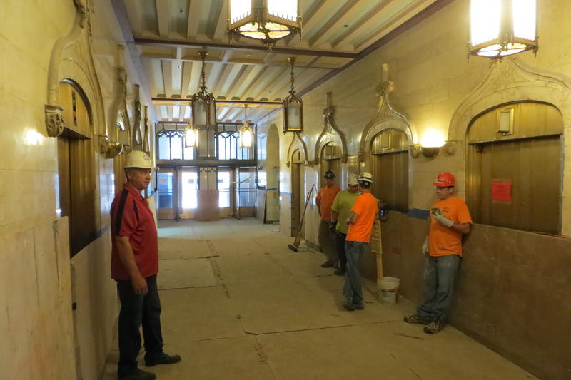 Workers wait for a lift in the lobby.