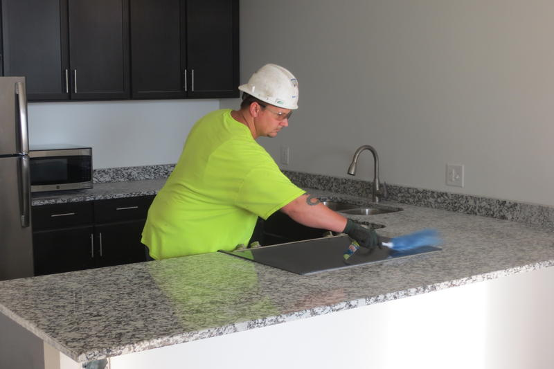 A worker shines a brand new granite counter top.
