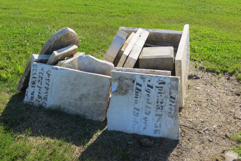 A pile of tombstones illustrate past neglect at Sams Cemetery.