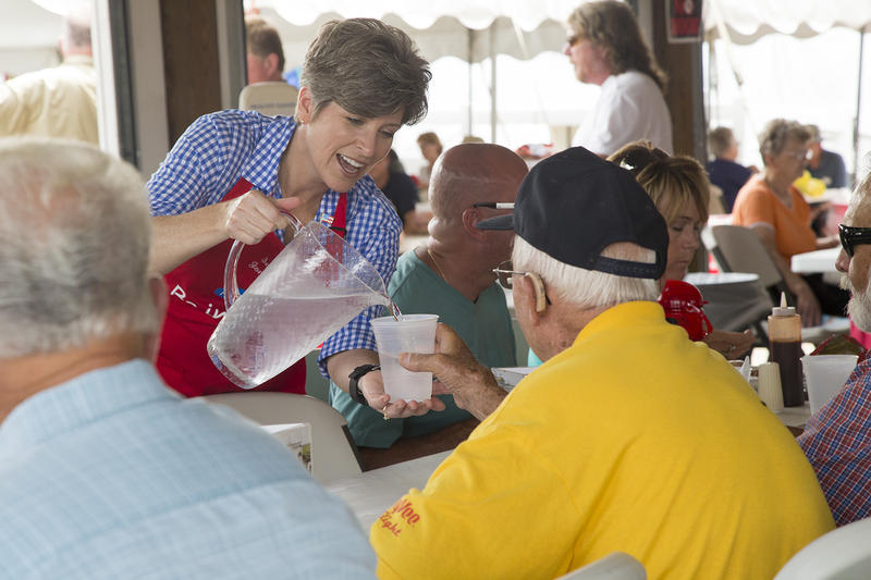 Sen. Joni Ernst (R-Iowa) fills a water glass for an Iowa State Fair visitor at the Iowa Pork Producers' tent.
