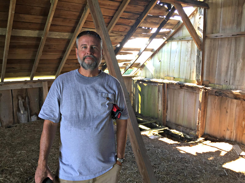Mike Hudson, standing in the hayloft of his current barn project, says he will deconstruct about 10-12 barns in the next year. He sells the reclaimed wood at his lumberyard in Elbert, Colo.