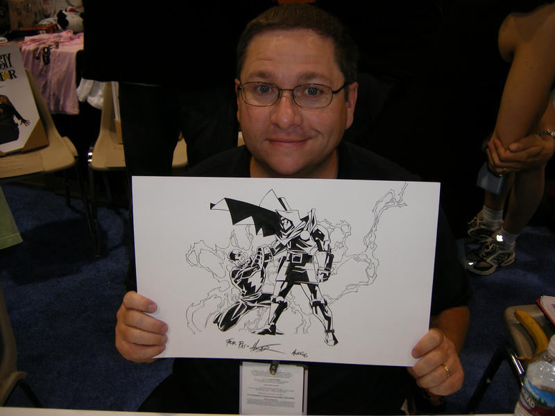 Illustrator Phil Hester holding his sketch of Dr. Doom vs Black Adam