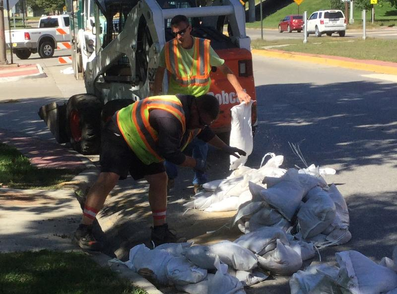 City workers remove sandbags from a storm drain.