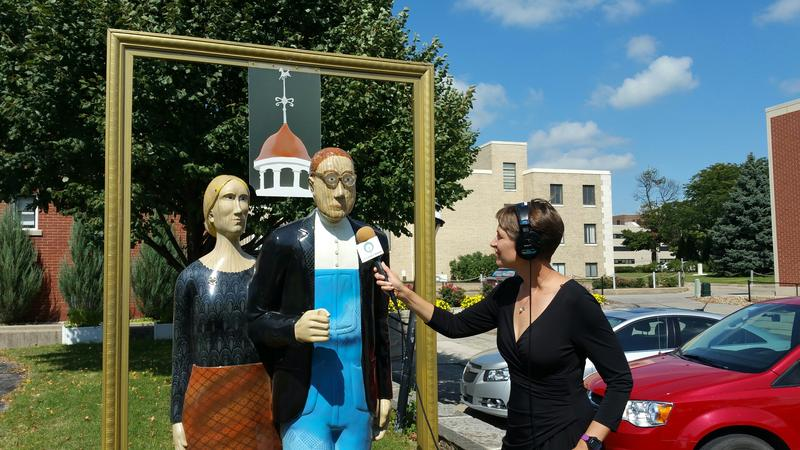 "Charity Nebbe attempts to get a comment from ""American Artist,"" on display in front of the Grant Wood studio in Cedar Rapids. The statue is part of ""Overalls All Over,"" a project marking the 125th anniversary of Grant Wood's birth."