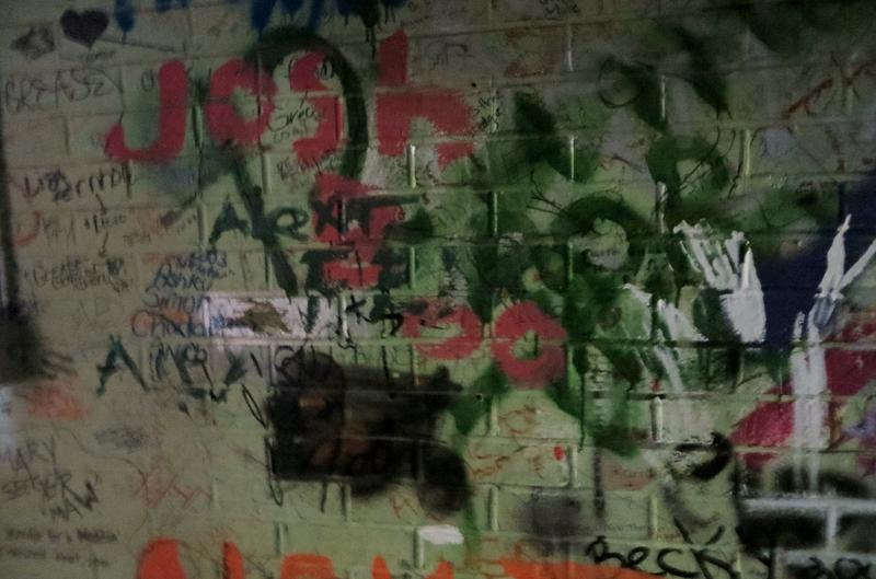"Graffiti and signatures in the ""green room"" behind the auditorium stage."
