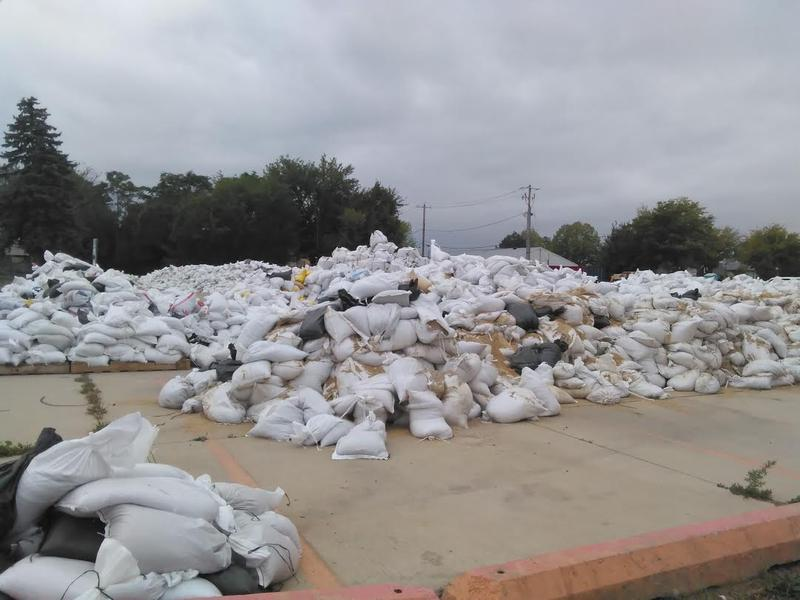 Sandbags used in temporary barriers are piled in the parking lot across from the NewBo City Market in Cedar Rapids.