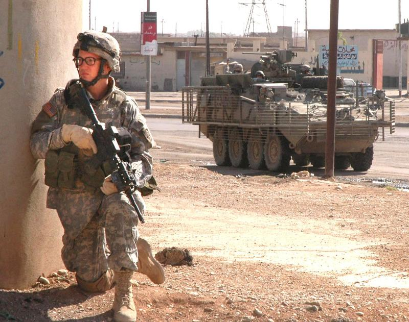 Spc. Kirk B. Hubbard, radio telephone operator, Company A, 4th Battalion, 23rd Infantry Regiment, 172nd Stryker Brigade Combat Team, Fort Richardson, Ala., uses a wall for cover while he pulls security during a patrol Oct. 20, 2005, in Mosul, Iraq.