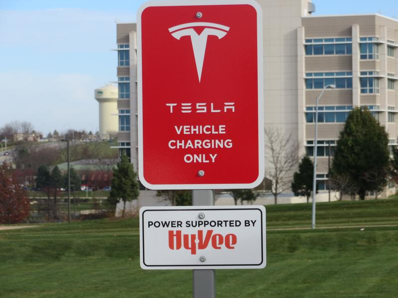 Placard announcing new Tesla charging stations at West Des Moines Hy-Vee store