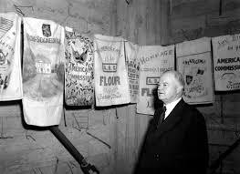 Herbert Hoover stands near WWI Belgian embroidered flour sacks.