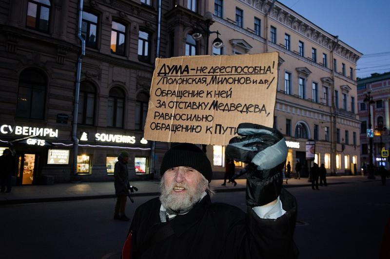 A protestor holds a sign calling for Russian Prime Minister Dmitry Medvedev's resignation.