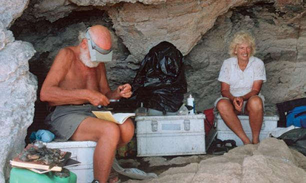 Peter and Rosemary Grant sit in a cave on Daphne Major Island in 2004. The cave generally was used for cooking. Here, Peter is shown measuring the beak of a finch.