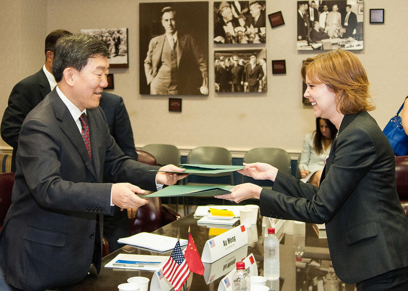 Darci Vetter (right), and Vice Minister, Minister of Agriculture, People's Republic of China Niu Dun (left) exchange copies of the U.S. China Joint Committee on Cooperation in Agriculture on Tuesday, Jun. 9, 2013.