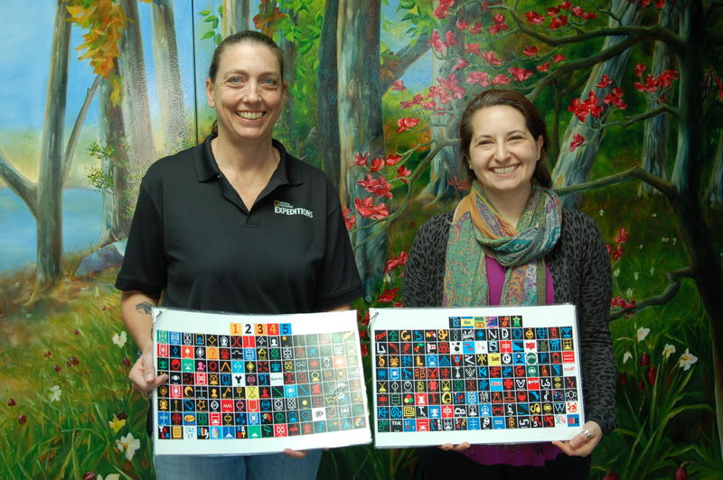 Iowa State University Primatologist Jill Pruetz and Phd Candidate Andrea Rabinowitz hold pages of the lexigram keyboard that bonobos use to communicate at the Ape Cognition and Conservation Initiative in Des Moines.