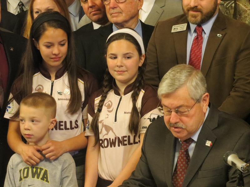 Gun rights activists Meredith and Natalie Gibson look on as Governor Branstad signs gun rights bill into law