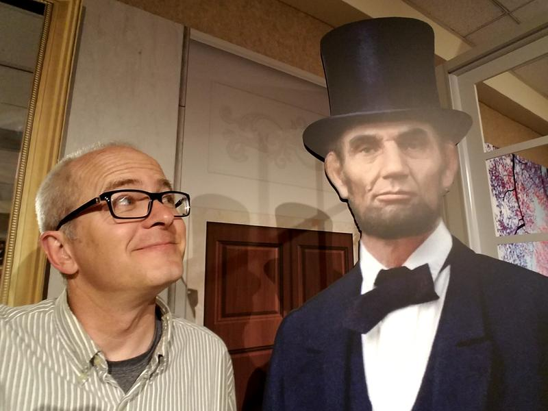 Host Ben Kieffer stands next to a cutout of Abraham Lincoln