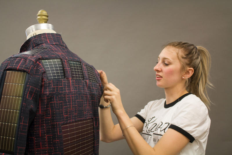 2017 ISU graduate Kathryn Kaalberg works on the prototype of a jacket containing solar panels she will present in Washington, D.C. this week.