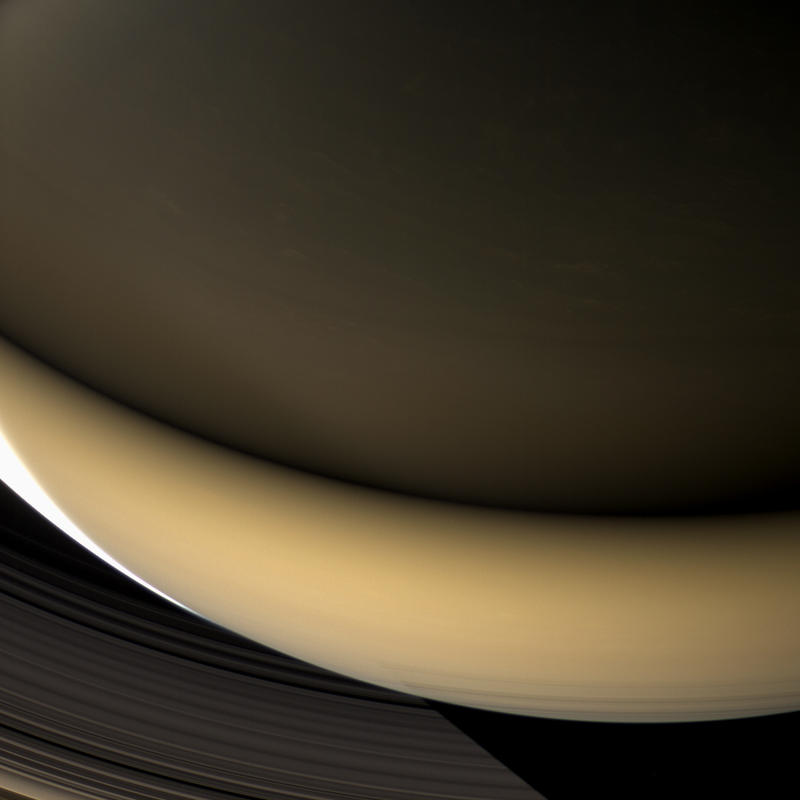 Some of Saturn's nightside illuminated by light reflecting from the rings, except for small sunlit crescent at left.  Top part getting less light because it is muted by the ring's particles.  Composite from 44 images taken by Cassini 4/23/2007.