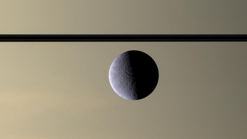 The dark line of Saturn's ringplane with the moon Rhea.  It has an icy landscape and may have its own rings, although they would be extremely thin. Composite from Cassini's photos taken 7/17/2007 from 770,000 miles away.