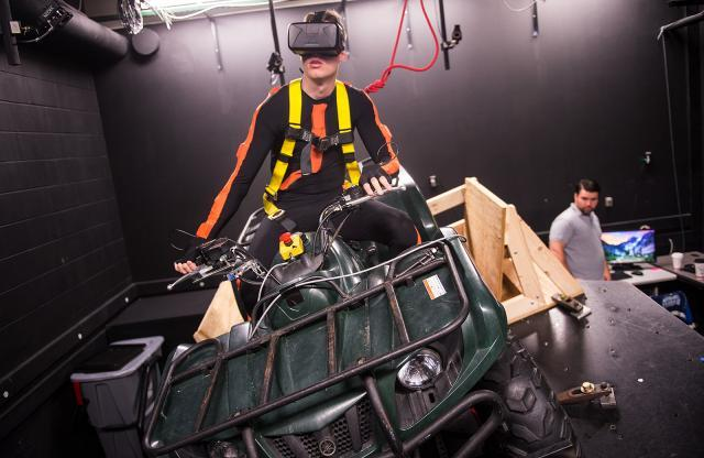 Kyle Losik rides the university's virtual reality ATV simulator. Losik's suit has 17 sensors that help researchers monitor his center of mass, which may shift and lead to a loss of control.