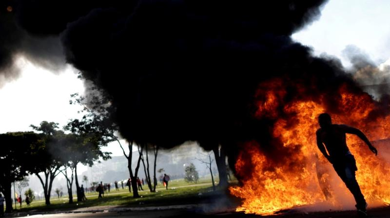 A demonstrator runs near a burning barricade during a protest against President Michel Temer and the latest corruption scandal to hit the country, in Brasilia, Brazil.
