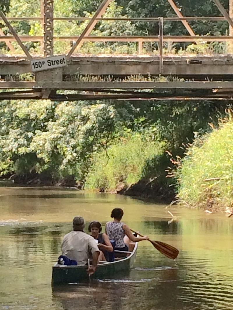 Jim Pease, Charity Nebbe, and Emily Woodbury paddling under the 150th Street Bridge over the Skunk River