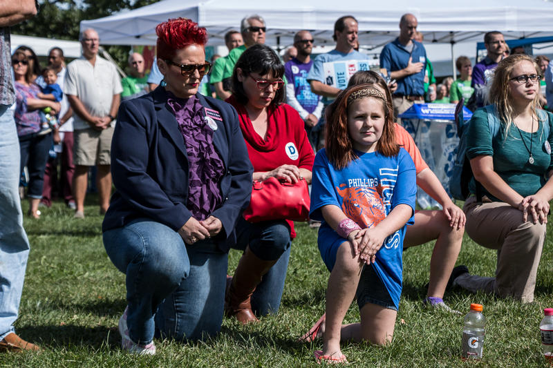 Iowa 3rd District congressional Democratic candidate Heather Ryan takes a knee during the National Anthem.